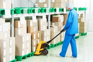 medical warehouse worker man loading boxes with medcine drugs by hand forklift